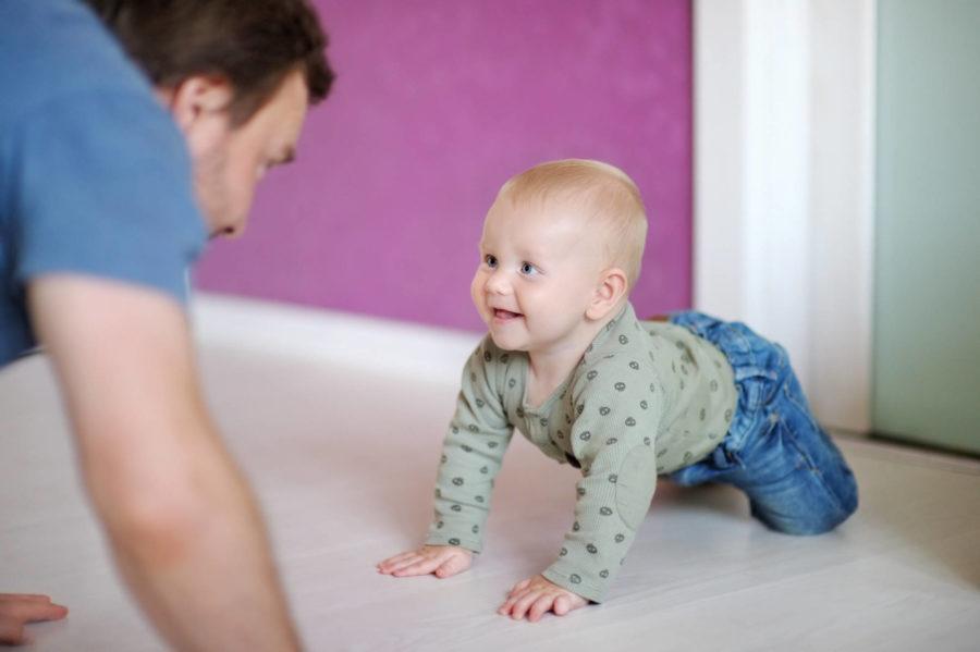 папа учит ребенка ползать